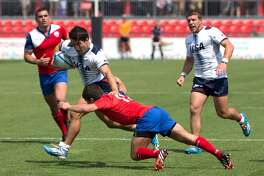 Team USA's Madison Hughes, center left, breaks a tackle from Chile's Juan Pablo Larenas, center right, during men's rugby sevens at the 2015 Pan Am Toronto games in Toronto, Saturday, July 11, 2015. (Chris Young/The Canadian Press via AP)