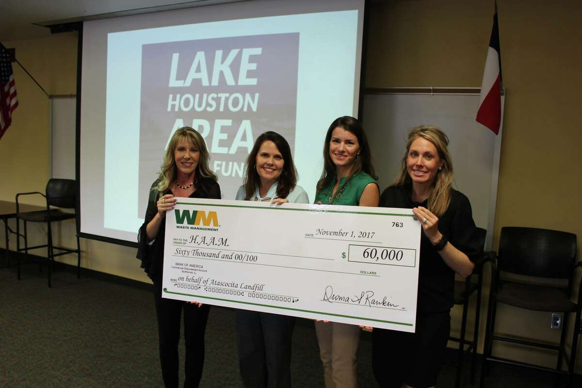 Representatives of Waste Management present a $60,000 check to the Lake Houston Relief Fund at the Atascocita BizCom meeting Thursday, Nov. 2.