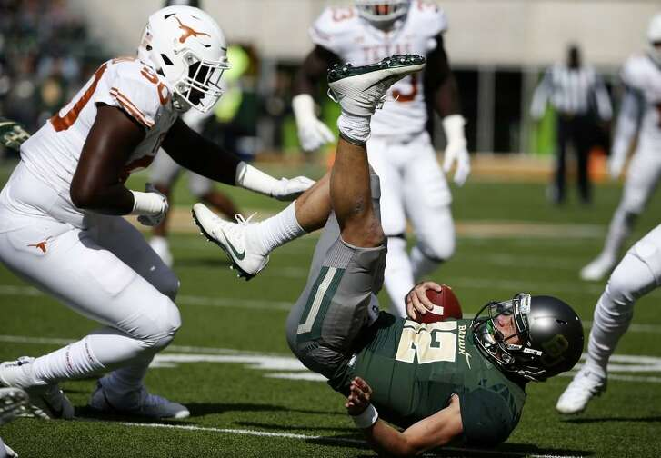 Charlie Brewer #12 of Baylor is knocked to the ground as Charles Omenihu #90 of Texas closes in during a game at McLane Stadium on Oct. 28, 2017 in Waco, Texas.
