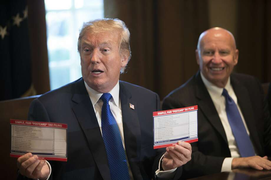 "President Donald Trump holds examples of what a ""postcard"" tax return might look like under the Republican tax plan alongside Rep. Kevin Brady (R-Texas), chairman of the House Ways and Means Committee, inside the Cabinet Room at the White House in Washington, Nov. 2, 2017. Photo: TOM BRENNER, NYT"