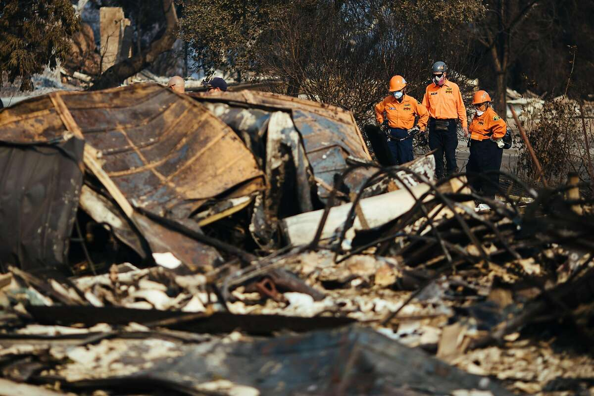 Search and rescue workers watch as the search and rescue dog combs through the rubble of a home on the Millbrook Drive on Friday, Oct. 13, 2017, in Santa Rosa, Calif.