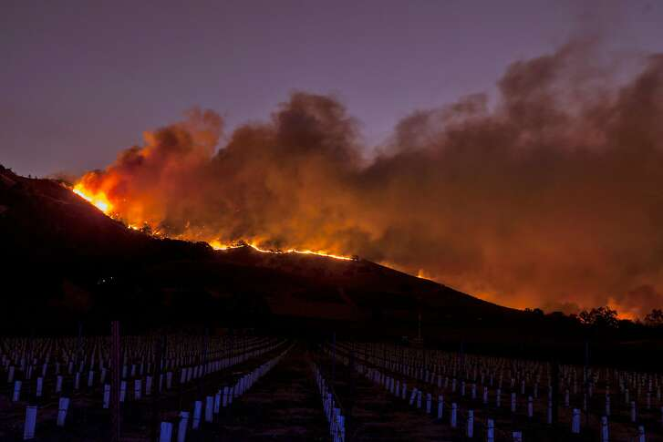 Flames moved through the hills above the Silverado Trail as a fast moving wind whipped wildfire raged though wine region in Napa,  Oct 9, 2017.
