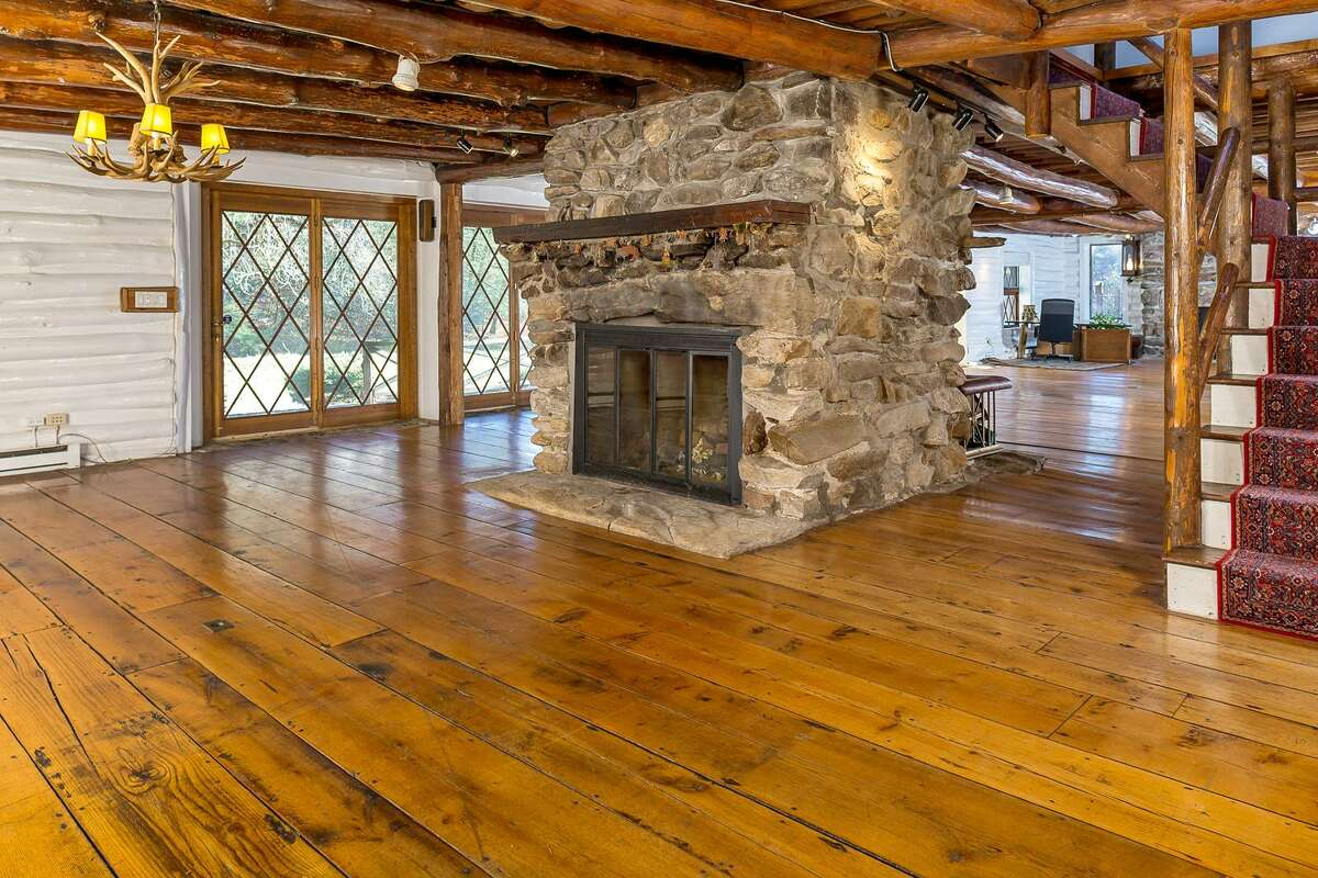 A rustic house at 38 Goodridge Road in Redding brings outdoor elements inside with antler and stone décor. There are wide beams and floor boards that give it a log cabin feel. Photo of the dining room.