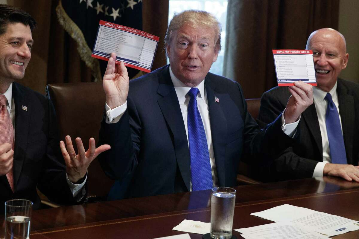 President Donald Trump holds an example of what a new tax form may look like during a meeting on tax policy with Republican lawmakers including House Speaker Paul Ryan of Wis., and Chairman of the House Ways and Means Committee Rep. Kevin Brady, R-Texas, right, in the Cabinet Room of the White House, Thursday, Nov. 2, 2017, in Washington.