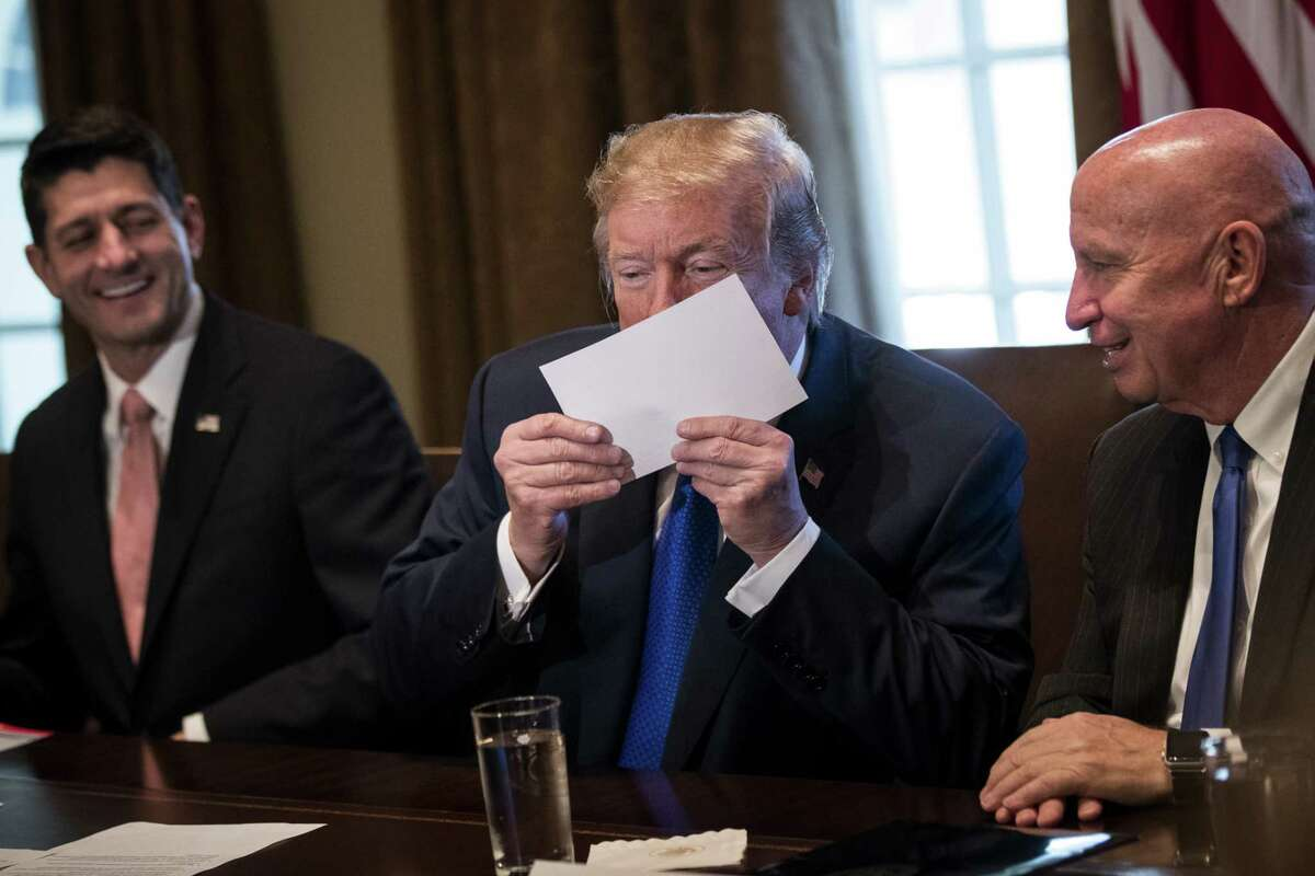 Flanked by Speaker of the House Paul Ryan and House Ways and Means Committee chairman Rep. Kevin Brady, R-Texas, President Donald Trump kisses an example of what a new tax form may look like as he speaks about tax reform legislation at the White House Thursday. Also on Thursday Republican lawmakers unveiled their plans for a massive rewrite of the U.S. tax code. (Drew Angerer/Getty Images)