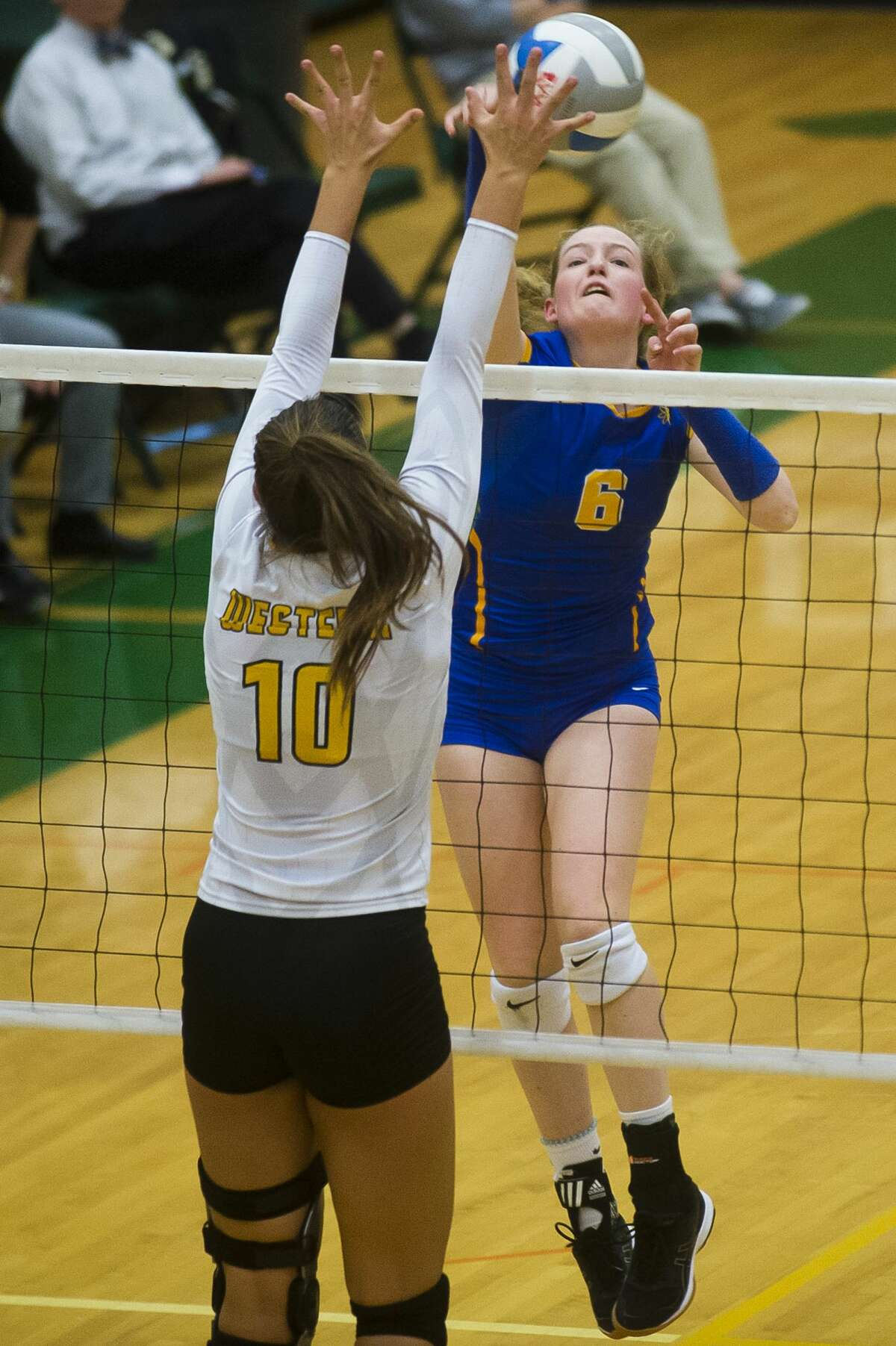 Midland junior Katherine Perry spikes the ball as Bay City Western senior Addison Bouza tries to block her during their Class A district final on Thursday, Nov. 2, 2017 at H. H. Dow High School. (Katy Kildee/kkildee@mdn.net)