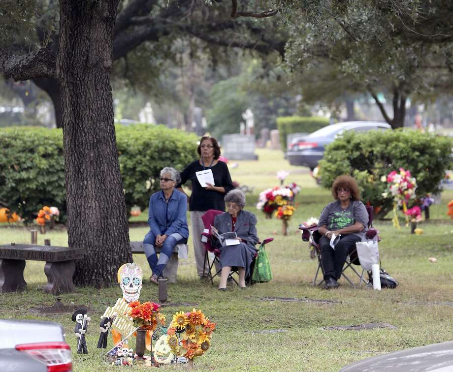 Susie Diaz (from left), Esther Zimmerlie, Guadalupe Alonzo and Terri Alonzo listen from a distance Thursday at San Fernando Cemetery No. 2 to the All Souls Day Mass given by Archbishop Gustavo Garcia-Sillar. Photo: William Luther /San Antonio Express-News / © 2017 San Antonio Express-News
