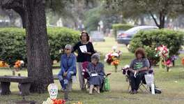 Susie Diaz (from left), Esther Zimmerlie, Guadalupe Alonzo and Terri Alonzo listen from a distance Thursday at San Fernando Cemetery No. 2 to the All Souls Day Mass given by Archbishop Gustavo Garcia-Sillar.