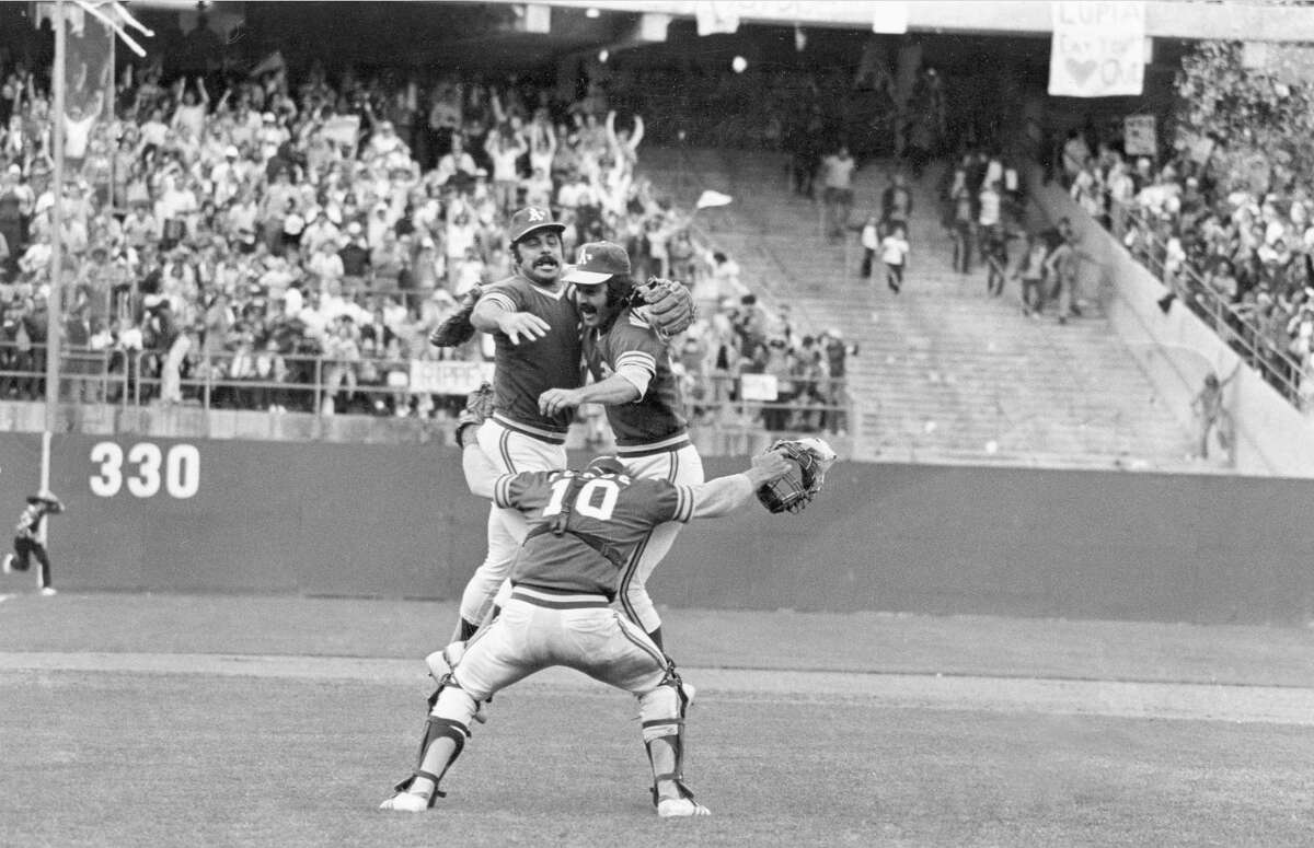 Oakland Athletics catcher Ray Fosse (10), Sal Bando, left, and pitcher Darold Knowles embrace each other after the A's beat the New York Mets, 5-2, to win the World Series in Oakland, Ca., Oct. 21, 1973. The A's capture the World Baseball Championship for the second time in a row. (AP Photo)