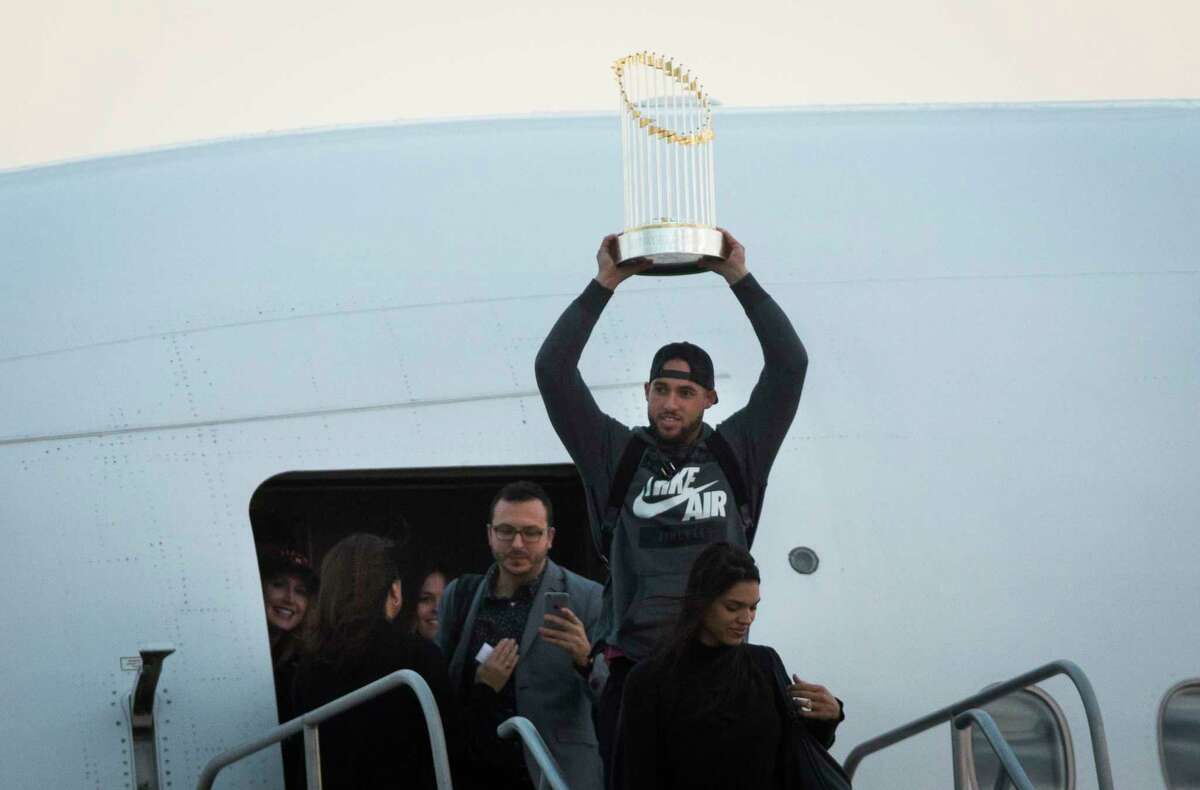 Houston Astros player George Springer arrives to Houston holding the Commissioner's Trophy, Thursday, Nov. 2, 2017, after winning the World Series against the Dodgers.