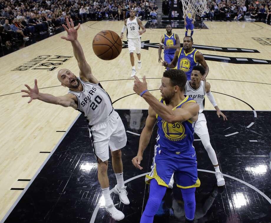 Golden State Warriors guard Stephen Curry (30) passes the ball past San AntonioSpursguard Manu Ginobili (20) during the first half of an NBA basketball game, Thursday, Nov. 2, 2017, in San Antonio. (AP Photo/Eric Gay)