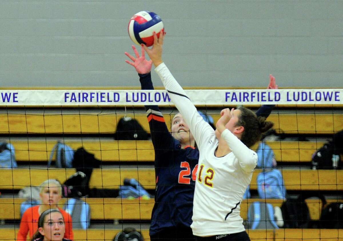 St. Joseph's Christina Crocco (12) taps the ball over the net as Danbury's Catrina Sullivan looks to block during FCIAC girls volleyball semifinal action in Fairfield, Conn., on Thursday Nov. 2, 2017.