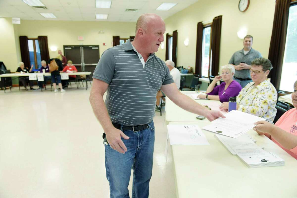 Milton Supervisor candidate Scott Ostrander receives his ballot as he votes at the Milton Community Center on Tuesday, Sept. 12, 2017, in Milton, N.Y. (Paul Buckowski / Times Union)