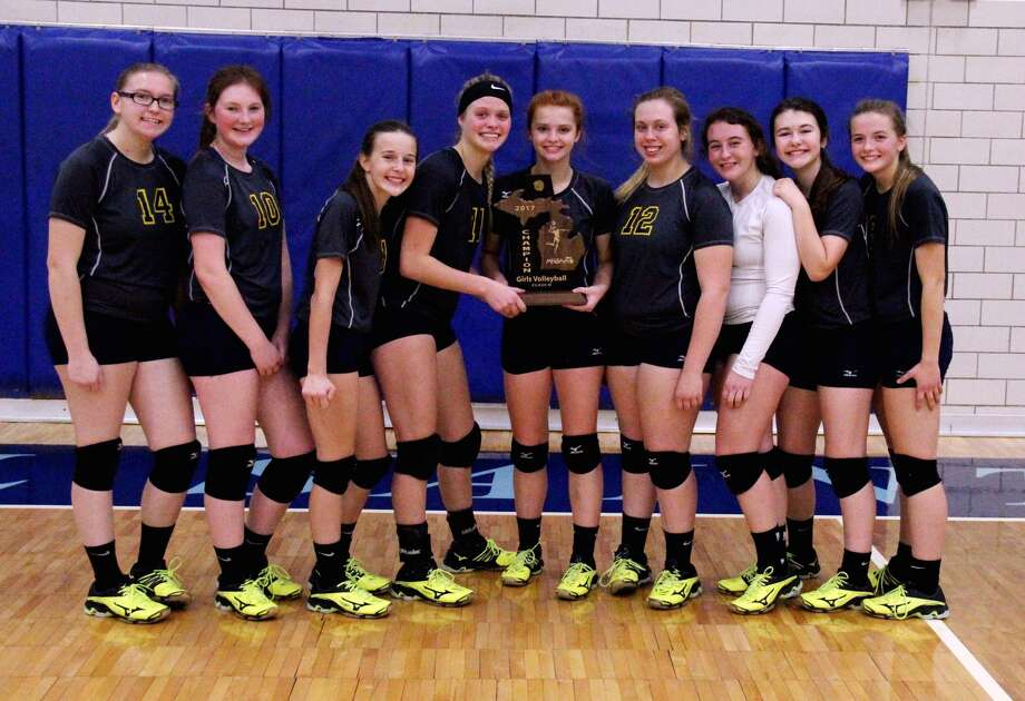 Members of the North Huron volleyball team pose with the Class D district championship trophy after defeating Caseville Thursday night in Bay City. It's the second straight district title for the Warriors. (Chip Burch/Huron Daily Tribune)