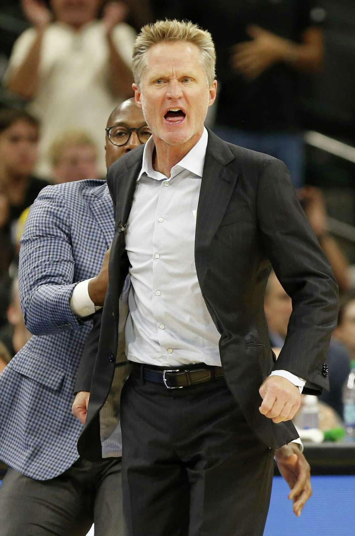 Golden State Warriors assistant coach Mike Brown (left) holds back head coach Steve Kerr as he reacts after a play during first half action against the San Antonio Spurs Thursday Nov. 2, 2017 at the AT&T Center. Kerr was given a technical.