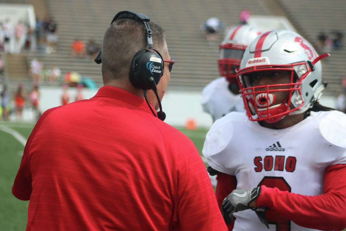Trojans head coach Dwayne Lane confers with Davion Williams during an earlier contest. Williams and Co. are celebrating the program's first winning district record in 10 years, following Thursday night's 42-7 win over the Texans.