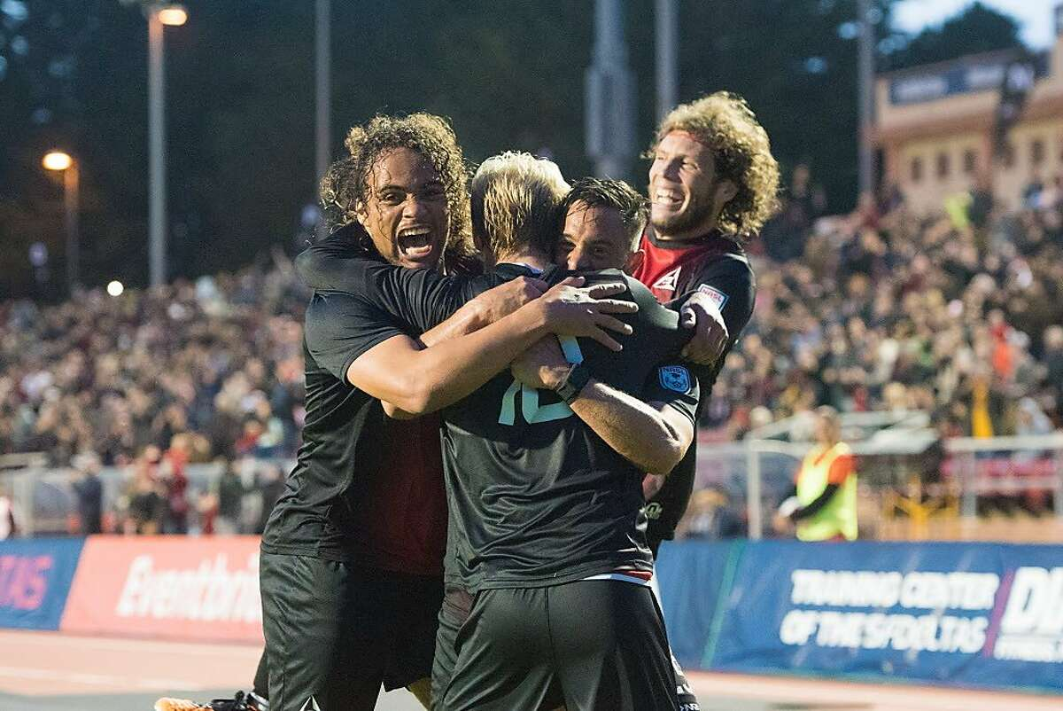 Teammates embrace Kyle Bekker (back to camera) after scoring the first goal in San Francisco Deltas history against the Indy Eleven on March 25, 2017 at Kezar Stadium in San Francisco. (Trevor Will)