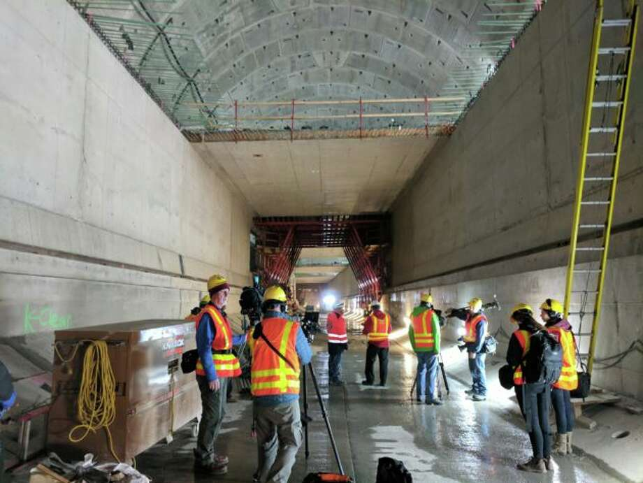 Members of the media capture the view of the roadway that is under construction inside the SR 99 tunnel on Thursday. Photo: Kurt Schlosser/GeekWire
