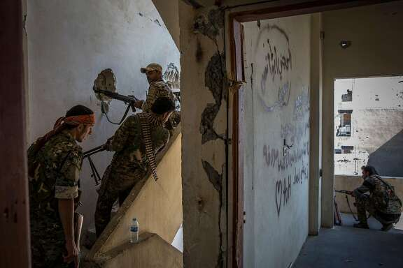 FILE -- Syrian Democratic Forces militiamen during the campaign to oust the Islamic State group from Raqqa, Syria, Oct. 12, 2017. Though its de facto capital has fallen, the Islamic State group appears ready to revert to its roots as a guerrilla force, and counterterrorism officials are bracing for a new wave of suicide attacks against civilians. (Ivor Prickett/The New York Times)