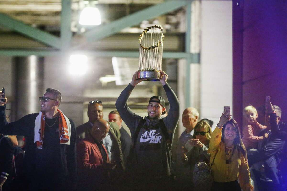 World Series Champions Houston Astros and MVP George Springer holds up the Championship trophy as they arrived to Minute Maid Park Thursday, Nov. 2, 2017, in Houston. Springer is a native of New Britain, Conn. His parents, George Jr. and Marie Springer still live on the end of a cul-de-sac up the hill from the Slade Middle School, where George III was a shy, slight boy with a stutter.