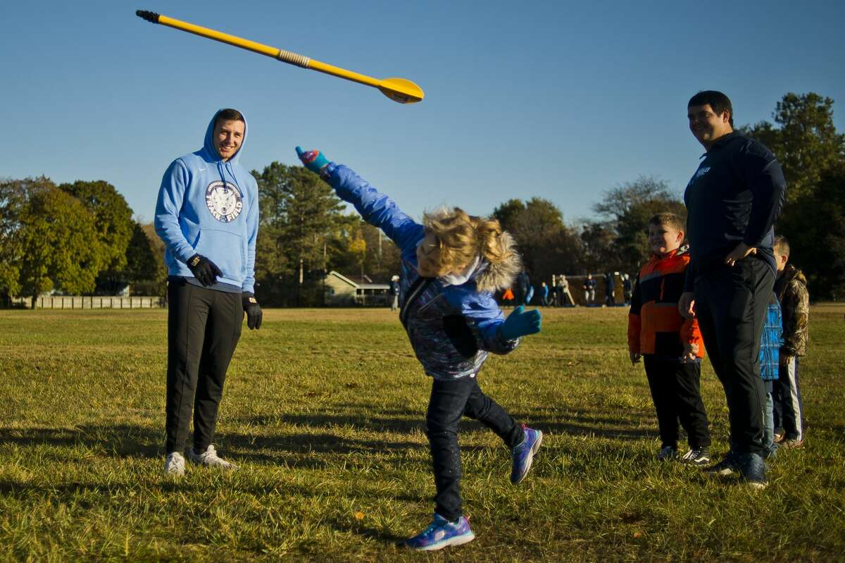 Northwood University track athlete Ben Quella, left, coaches Grace Pilgrim, 7, as she throws a javelin during