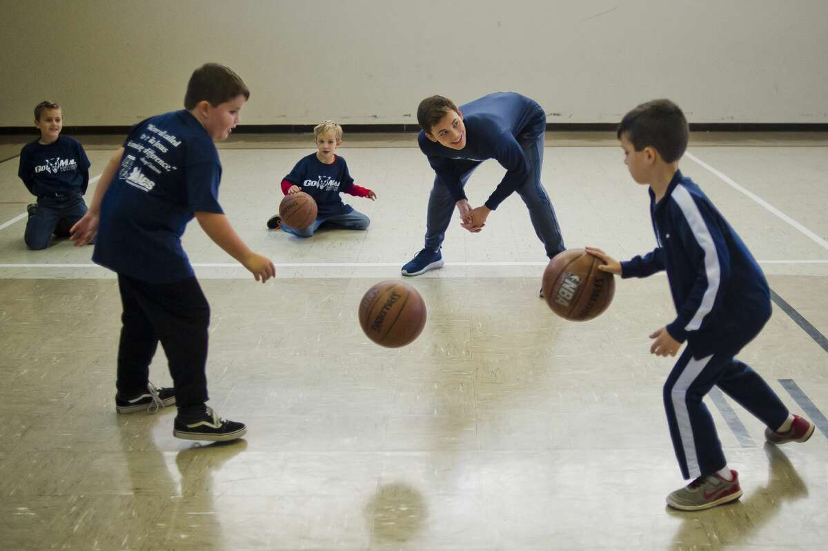 Northwood University basketball player Nate Georgeton, second from right, instructs a group of kids in basketball during