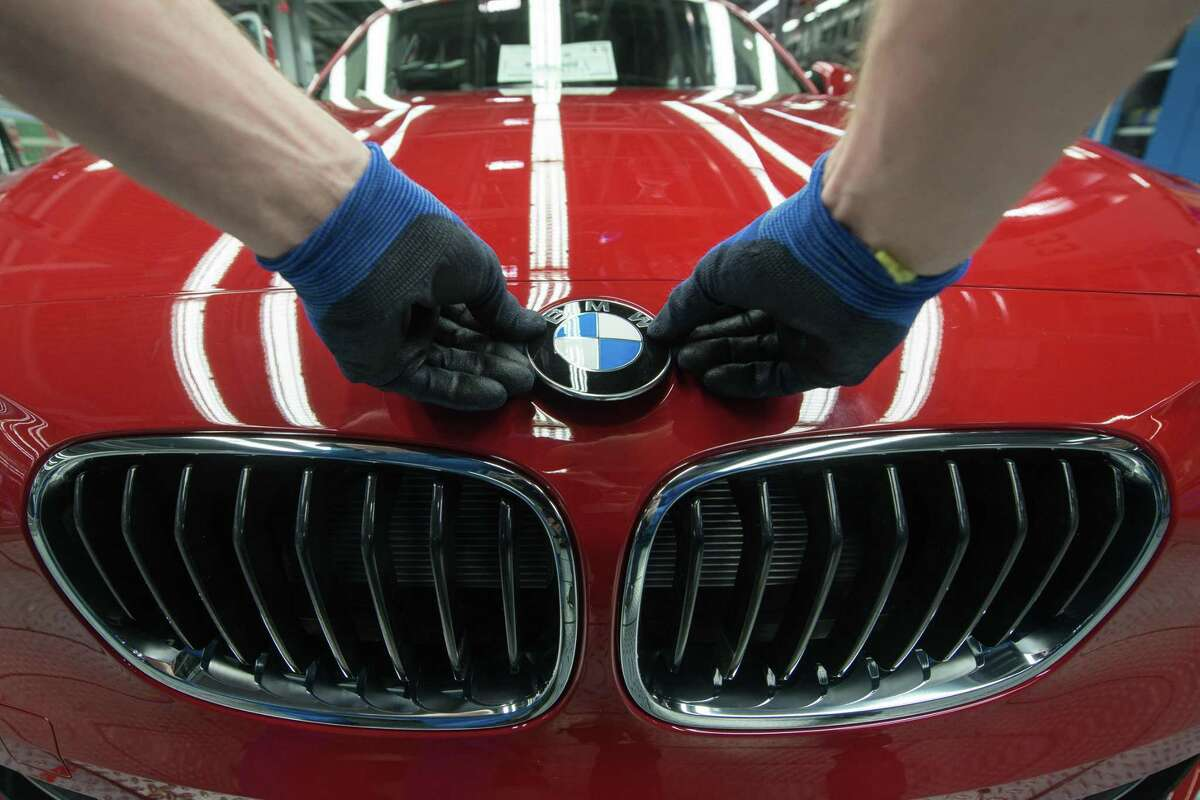 A worker fixes the logo of German car maker BMW on a BMW car at the company's plant in Regensburg, southern Germany. The luxury carmaker on Friday said it was recalling
