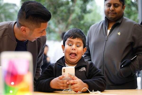 A boy makes faces while testing out the Animoji feature on an iPhone X at the Apple Store Union Square on November 3, 2017, in San Francisco, California. Apple's flagship iPhone X hits stores around the world as the company predicts bumper sales despite the handset's eye-watering price tag, and celebrates a surge in profits. / AFP PHOTO / Elijah NouvelageELIJAH NOUVELAGE/AFP/Getty Images