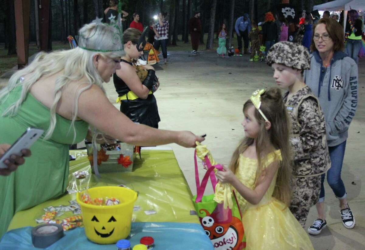 Shepherd Public Library Head Director Helenmarie Johnson (left), dressed as Glinda the Good Witch of the North gives some candy to Olivia Whitworth (middle), who is dressed as Princess Belle from Beauty and the Beast and her brother Nathan Whitworth (right), who is dressed as an Army Ranger.