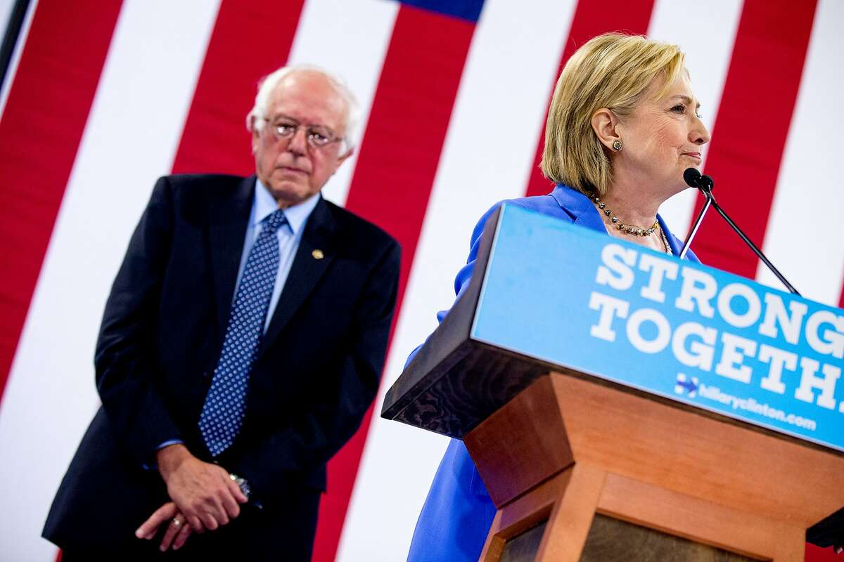 Democratic presidential candidate Hillary Clinton accompanied by Democratic presidential candidate Sen. Bernie Sanders, I-Vt., left, speaks as Sanders endorses Clinton at a rally at Portsmouth High School in Portsmouth, N.H., Tuesday, July 12, 2016. (AP Photo/Andrew Harnik)
