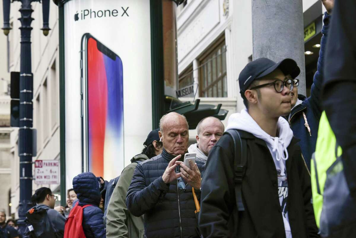 An advertisement is displayed as customers wait in line outside a store ahead of the sales launch for the Apple Inc. iPhone X smartphone in San Francisco, California on Friday. The $1,000 price tag on Apple Inc.'s new iPhone X didn't deter throngs of enthusiasts around the world who waited - sometimes overnight - in long lines with no guarantee they would walk out of the store with one of the coveted devices.