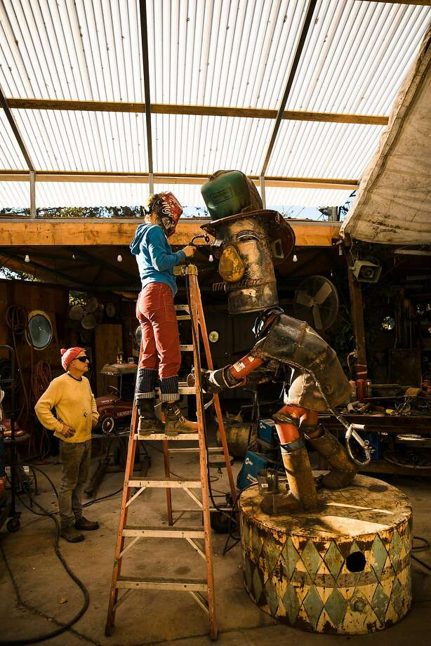 Mathilde Amiot sands off the rough edges as Patrick Amiot inspects the fireman sculpture at his workshop in Sebastopol. Photo: Mason Trinca, Special To The Chronicle