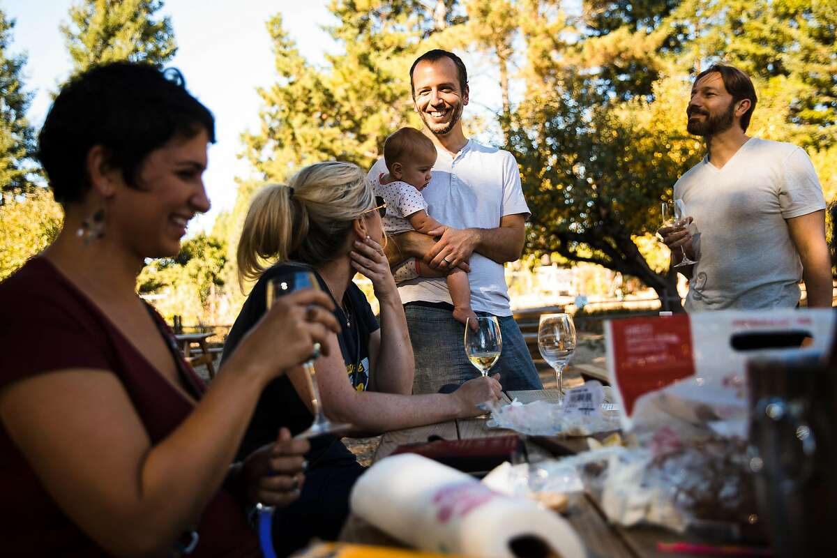 From the left, Stefanie Dombek, Jennifer Lund, Steve Dombek with his nine-month-old son, Remy Dombek, and Dave Hearn enjoy themselves on back patio of Horse and Plow in Sebastopol, Calif. Saturday, October 28, 2017.