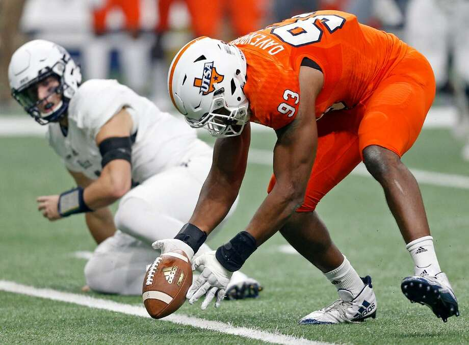 UTSA defensive end Marcus Davenport (93) picks up a fumble by Rice quarterback Sam Glaesmann (4), left, during a game at the Alamodome on Oct. 21, 2017. Photo: Edward A. Ornelas /Express-News