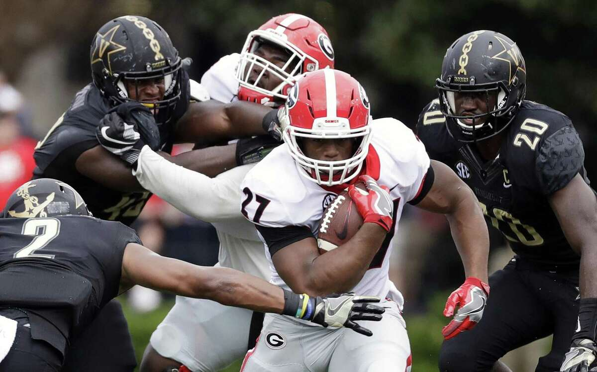 In this Oct. 7, 2017, file photo, Georgia tailback Nick Chubb (27) gets past Vanderbilt safety Arnold Tarpley III (2) during the first half of an NCAA college football game in Nashville, Tenn.