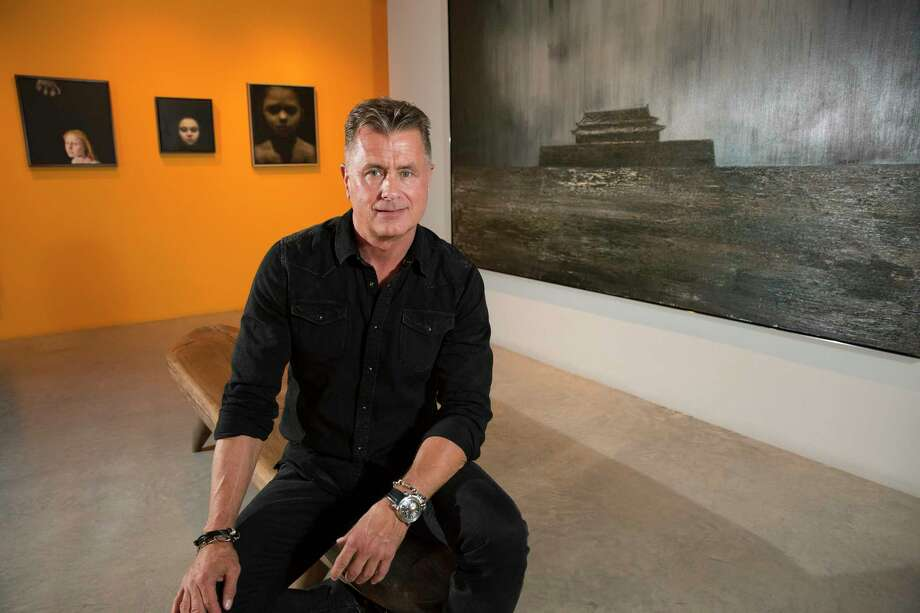 """Christie, sitting in front of a large painting (at right) by Duan Jianghua, """"Castle No. 1"""" (Forbidden City). Photo: Yi-Chin Lee, Houston Chronicle / © 2017  Houston Chronicle"""