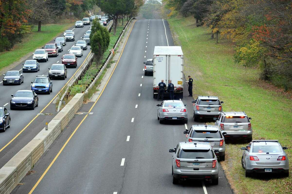 Police inspect the tractor trailer that was involved in the fatal accident on the Merritt Parkway, right, as southbound traffic crawls forward in Greenwich, Conn. on Thursday, Nov. 2, 2017.