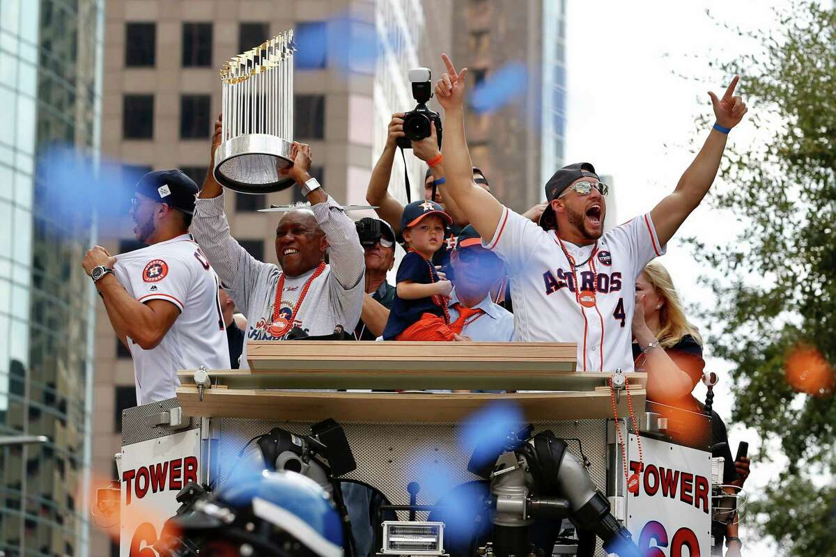 Houston mayor Sylvester Turner holds up the World Series trophy, while George Springer (4) cheers to the crowd during the parade.