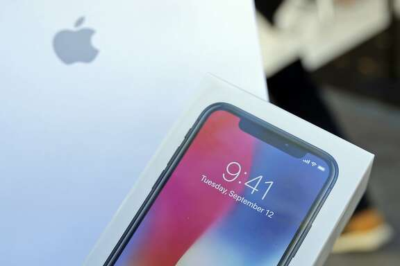 A shopper shows his purchased iPhone X, Friday, Nov. 3, 2017, in Miami Beach, Fla. Apple's iPhone X went on sale Friday, as the company scrambles to meet demand for a marquee device that sports a lush screen, facial-recognition skills and a $1,000 price tag. (AP Photo/Alan Diaz)