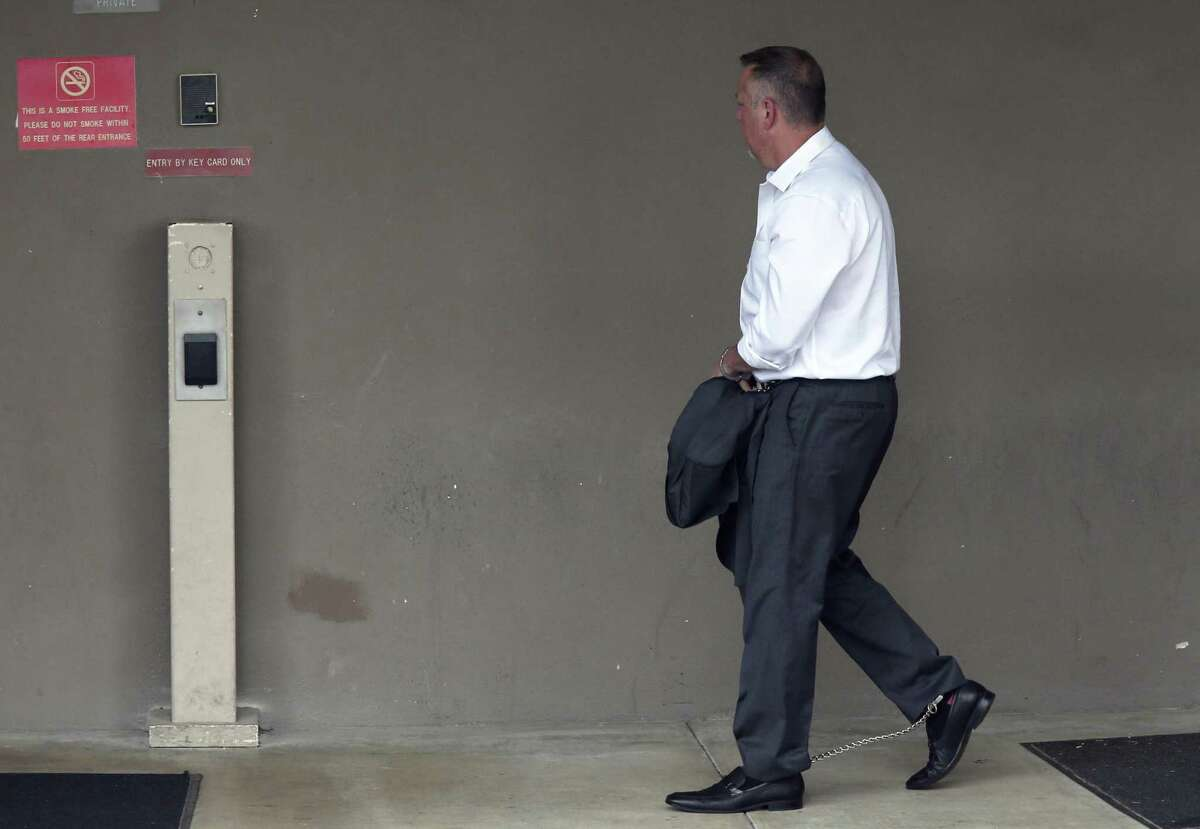 A handcuffed Stan Bates makes his way into the San Antonio federal courthouse on May 17 following his arrest. He and state Sen. Carlos Uresti are accused of defrauding investors with FourWinds Logistics, a now-defunct frac-sand company. Bates was FourWinds CEO and Uresti served as outside legal counsel for a short time.