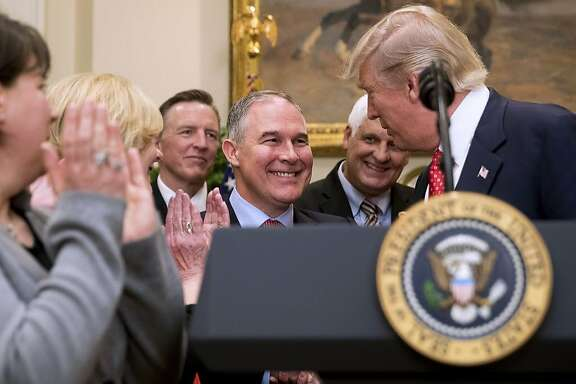 President Donald Trump shakes hands with Environmental Protection Agency (EPA) Administrator Scott Pruitt, center, before signing the Waters of the United States (WOTUS) executive order, Tuesday, Feb. 28, 2017, in the Roosevelt Room in the White House in Washington, which directs the Environmental Protection Agency to withdraw the Waters of the United States (WOTUS) rule, which expands the number of waterways that are federally protected under the Clean Water Act. (AP Photo/Andrew Harnik)