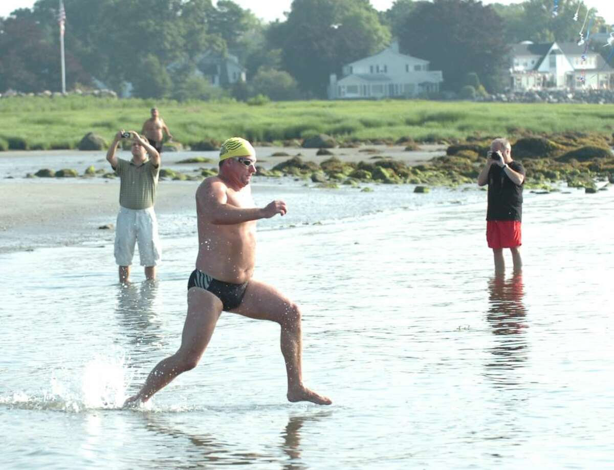 A swimmer enters Long Island Sound during the start of the Greenwich-Stamford Swim Across America event, dedicated to raising money and awareness for cancer research through swimming at Greenwich Point, Saturday morning, June 26, 2010.