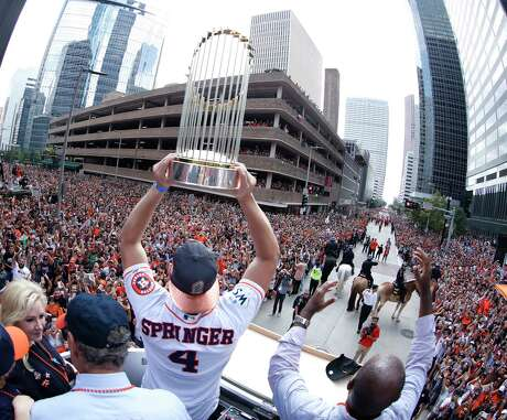 Houston Astros World Series MVP George Springer holds up the trophy as he and Carlos Correa joined Mayor Sylvester Turner and Astros owner Jim Crane in the bucket truck of HPD Tower truck 69 during the Houston Astros World Series victory parade downtown on Friday, Nov. 3, 2017, in Houston. Photo: Karen Warren, Houston Chronicle / © 2017 Houston Chronicle