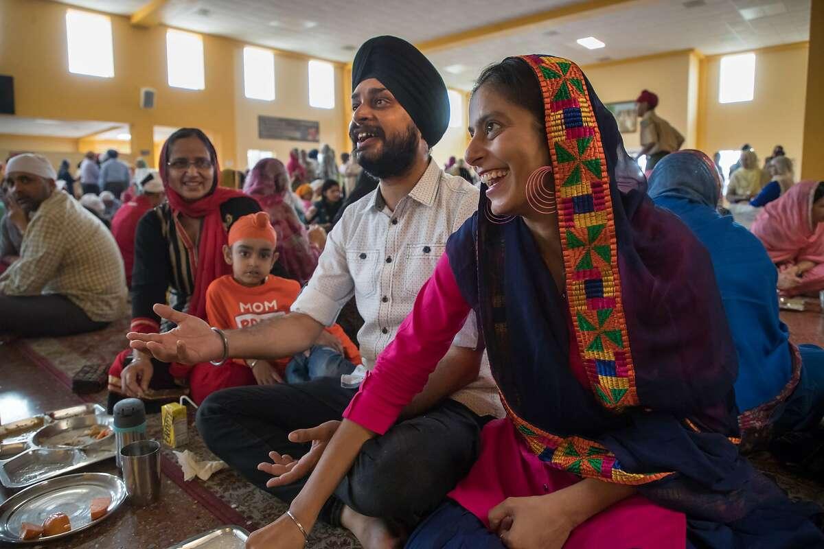 Harpreet Singh, an H-1B visa holder, has lunch with his wife Gurvindler Kaur, right, mother Jasvinder Kaur, left, and Sunjam Singh, 4 at Gurdwara, an Indian temple, on Sunday, Oct. 29, 2017, in San Jose, Calif.