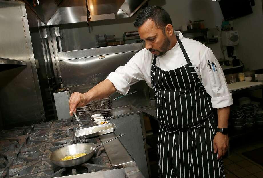 Chef Manish Tyagi prepares seasoning for potatoes at August 1 Five. Photo: Liz Hafalia, The Chronicle