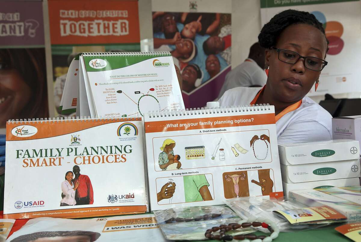 """In this photo taken Tuesday, Sept. 26, 2017, health worker Sylvia Marettah Katende displays reproductive health products and information at a family planning exhibition in Kampala, Uganda. Over half of the world's population growth between now and 2050 will take place in Africa and Uganda, a leader in taking on global health issues like AIDS, is turning to """"champion men"""" to promote vasectomies in family planning. (AP Photo/Stephen Wandera)"""