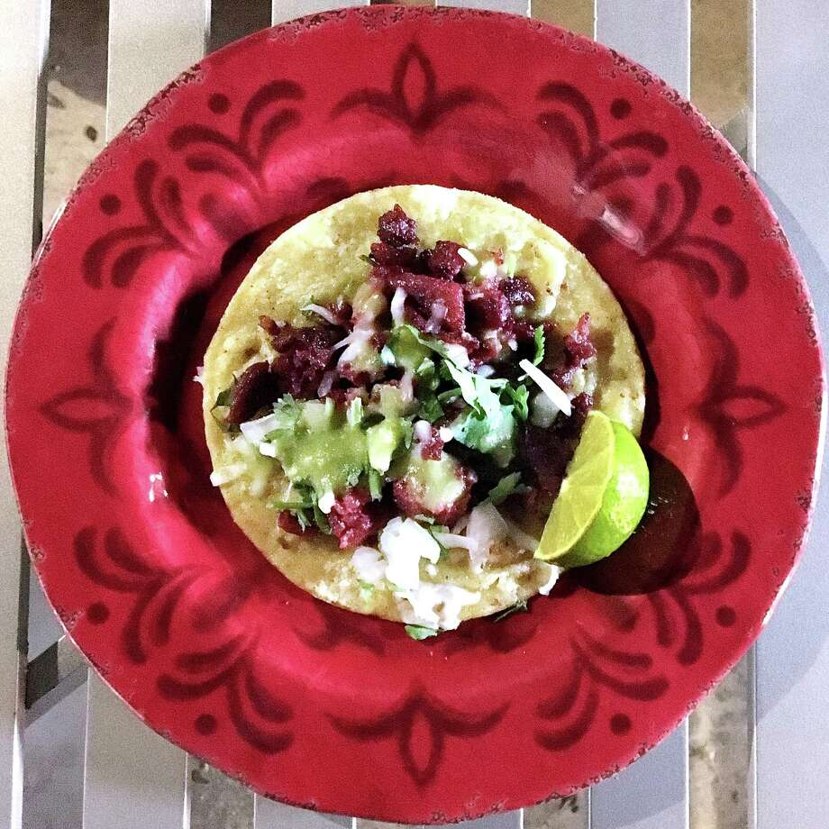 All pastor taco on a corn tortilla with onions, cilantro and cheese from the Tacos de Güero truck. Photo: Mike Sutter /San Antonio Express-News