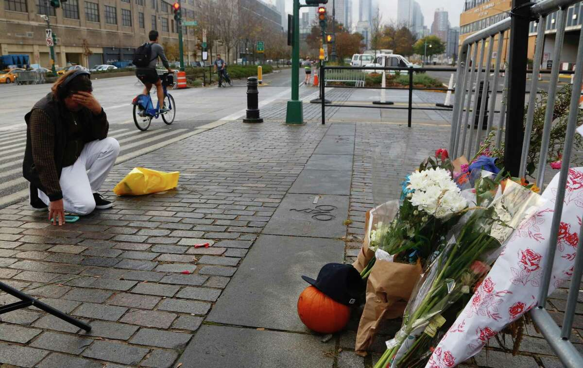 A man kneels Thursday in front of a makeshift memorial in honor of Tuesday's victims of a bike path attack in New York. Several people were killed and others injured after a truck driver drove onto the path along New Yorks Hudson River.