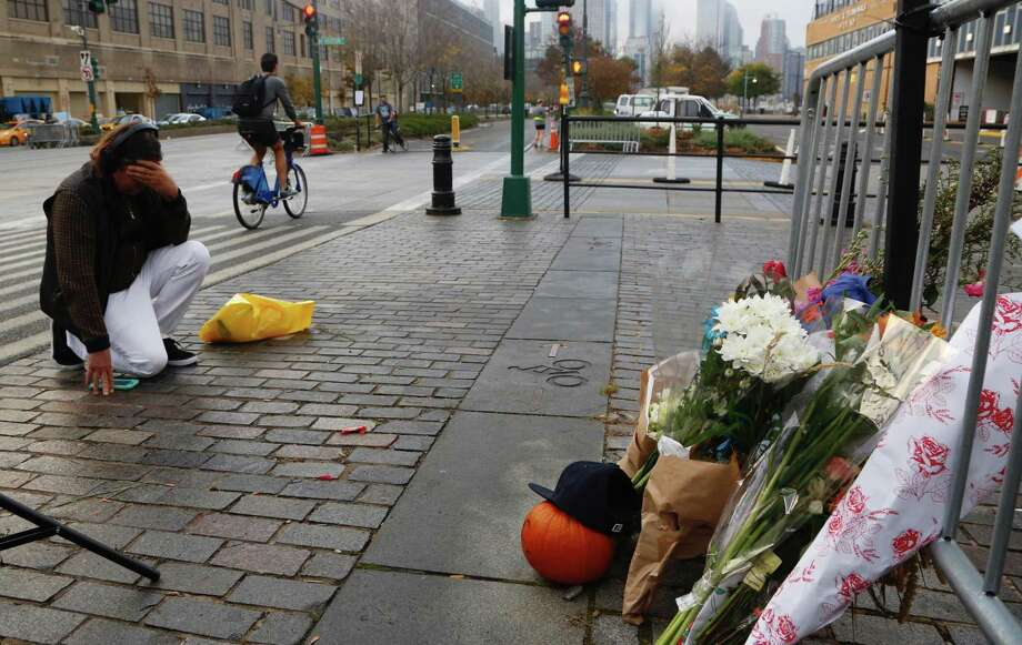 A man kneels Thursday in front of a makeshift memorial in honor of Tuesday's victims of a bike path attack in New York. Several people were killed and others injured after a truck driver drove onto the path along New Yorks Hudson River. Photo: Mark Lennihan /Associated Press / AP