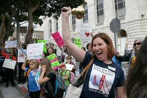 Third grade teacher Sheila Tenney (rings bell) from Glen Park school joins the teacher's protest across the street from district headquarters for a fair contract on Tuesday, October 10, 2017, in San Francisco, Calif.   The union scheduled a strike vote for November after their contract expired several months ago.